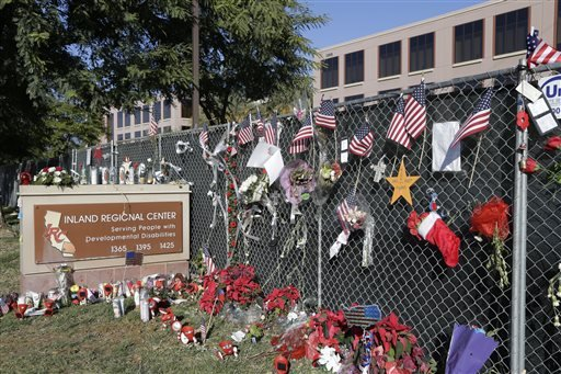 Dec. 29, 2015, photo, flowers and American flags honoring the victims of the attack on Dec. 2 are placed outside the Inland Regional Center where the fatal shooting took place in San Bernardino, Calif. (AP Photo/ Nick Ut)