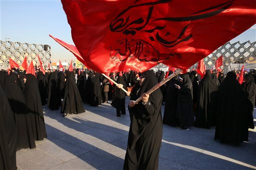 """Iranian women wave flags that read, """"Death to America and we shall never accept humiliation,"""" during a rally to protest the execution by Saudi Arabia last week of Sheikh Nimr al-Nimr, a prominent opposition Saudi Shiite cleric, in Tehran, Iran, Monday, Ja"""