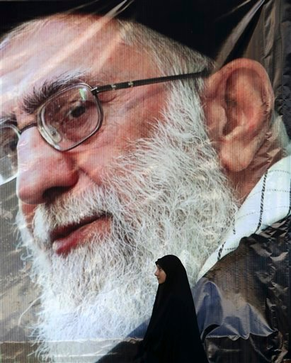 An Iranian woman stand under a portrait of the Supreme Leader Ayatollah Ali Khamenei at the conclusion of a rally to protest the execution last week of Sheikh Nimr al-Nimr, a prominent opposition Shiite cleric, shown in the posters, in Tehran, Iran, Monda