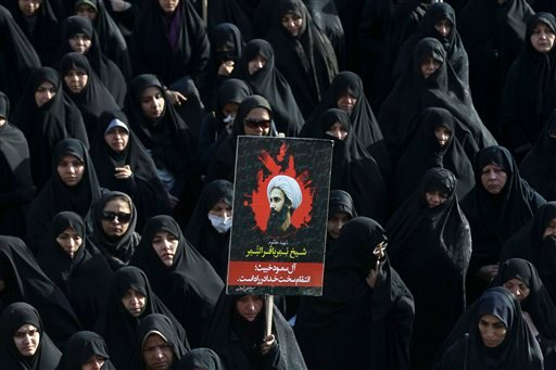 An Iranian woman holds up a poster showing Sheikh Nimr al-Nimr, a prominent opposition Saudi Shiite cleric who was executed last week by Saudi Arabia, in Tehran, Iran, Monday, Jan. 4, 2016. Allies of Saudi Arabia followed the kingdom's lead and began scal