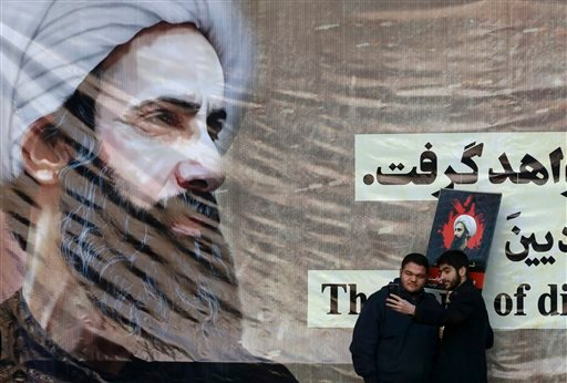 Iranian men take a selfie with a poster of Sheikh Nimr al-Nimr, a prominent opposition Saudi Shiite cleric, who was executed last week by Saudi Arabia, at the conclusion of a rally protesting his execution, in Tehran, Iran, Monday, Jan. 4, 2016. Allies of