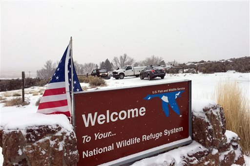 An sign of the National Wildlife Refuge System is seen at an entry of the wildlife refuge, where some vehicles are seen used to block access to the inside of the refuge, about 30 miles southeast of Burns, Ore., Sunday, Jan. 3, 2016. Armed protesters are o