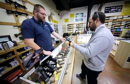 Mike Howse, left, helps David Foley as he shops for a handgun at the Spring Guns and Ammo store Monday, Jan. 4, 2016, in Spring, Texas. (AP Photo/David J. Phillip)