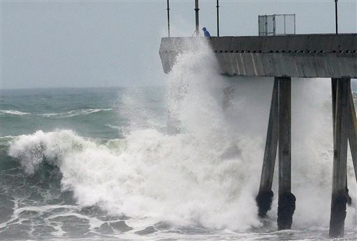A man stands near crashing waves on the Pacifica Pier in Pacifica, Calif., Tuesday, Jan. 5, 2016. El Nino storms lined up in the Pacific, promising to drench parts of the West for more than two weeks and increasing fears of mudslides and flash floods in r