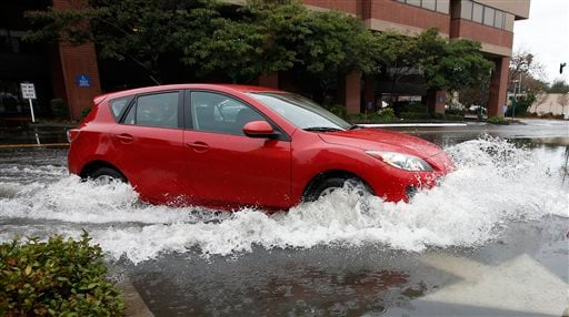 A car navigates through a flood water as it turns into a parking lot Tuesday, Jan. 5, 2016, in Sacramento, Calif. El Nino storms lined up in the Pacific promise to drench parts of the West for more than two weeks and increase fears of mudslides and flash