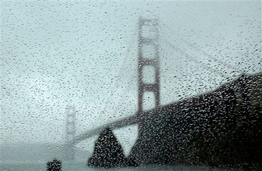 Rain drops bead on a car window below the Golden Gate Bridge Tuesday, Jan. 5, 2016, in Sausalito, Calif. El Nino storms lined up in the Pacific, promising to drench parts of the West for more than two weeks and increasing fears of mudslides and flash floo