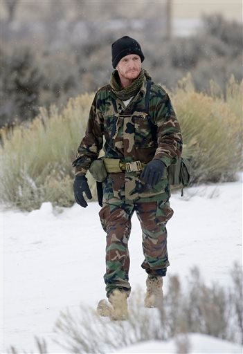 A member of the group occupying the Malheur National Wildlife Refuge headquarters, walks to the front gate Tuesday, Jan. 5, 2016, near Burns, Ore. Law enforcement had yet to take any action Tuesday against the group numbering close to two dozen who are up