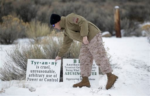 Jon Ritzheimer, of Arizona, a member of the group occupying the Malheur National Wildlife Refuge headquarters, adjust a sign Tuesday, Jan. 5, 2016, near Burns, Ore. Law enforcement had yet to take any action Tuesday against the group numbering close to tw