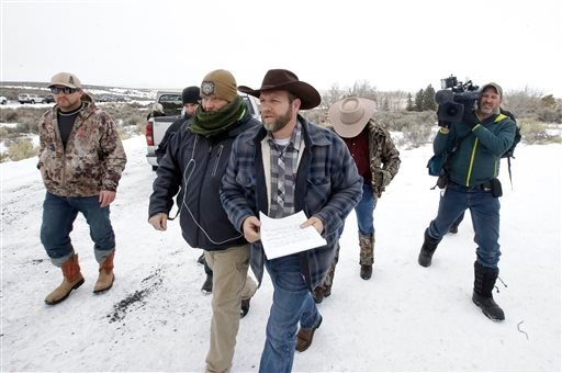 Ammon Bundy, center, one of the sons of Nevada rancher Cliven Bundy, arrives for a news conference at Malheur National Wildlife Refuge Tuesday, Jan. 5, 2016, near Burns, Ore. Law enforcement had yet to take any action Tuesday against a group numbering clo