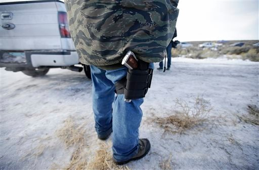 Sean Anderson, of Idaho, a supporter of the group occupying the Malheur National Wildlife Refuge, stands by the front gate Wednesday, Jan. 6, 2016, near Burns, Ore. With the takeover entering its fourth day Wednesday, authorities had not removed the group