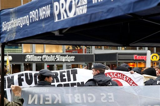 Protesters of the right-wing PRO NRW party, front, guarding policemen, center, and counter demonstrators, background, stand in front of the main station in Cologne, Germany, Wednesday, Jan. 6, 2016. More women have come forward alleging they were sexually