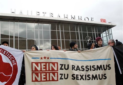 """People protest in front of the main station in Cologne, Germany, on Wednesday, Jan. 6, 2016. The poster reads: """"No to Racism, No to Sexism"""". More women have come forward alleging they were sexually assaulted and robbed during New Year's celebrations in th"""