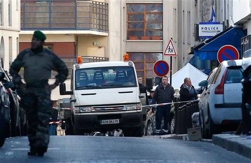 Police officers stand by the police station, seen in background right, after officers shot and killed a knife-wielding man wearing a fake explosives vest, in Paris, Thursday, Jan. 7, 2016. Officers shot and killed a knife-wielding man wearing a fake explo