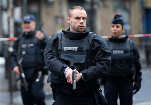 Police officers secure the perimeter near the scene of a fatal shooting which took place at a police station in Paris, Wednesday, Jan. 7, 2016. French officials say a man armed with a knife was shot to death by officers at a police station in northern Par