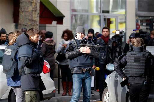 Police officers secure the area after a fatal shooting took place at a police station in Paris, Thursday, Jan. 7, 2016. Officers shot and killed a knife-wielding man wearing a fake explosive vest at a police station in northern Paris on Thursday, French o