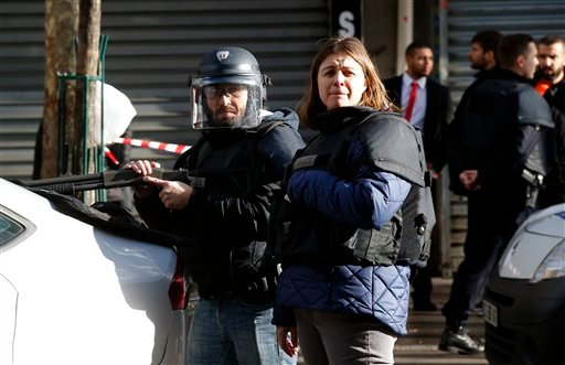 Police officers take position after a fatal shooting which took place at a police station in Paris, Thursday, Jan. 7, 2016. Officers shot and killed a knife-wielding man with wires protruding from his clothes at a police station in northern Paris on Thurs
