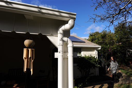 Roof gutters and pipes capture rain from the roof of a home in North Hollywood, Calif., Thursday, Jan. 7, 2016, and the water gets stored in a cistern for landscape watering during dry days.
