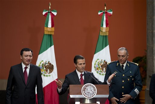 Mexican President Enrique Pena Nieto, flanked by Interior Minister Miguel Angel Osorio Chong, left, and National Defense Secretary Slavador Cienfuegos Zepeda gestures to thank members of his government and security forces.