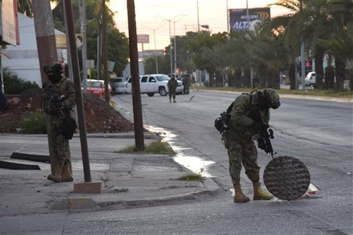 """A Mexican navy marine inspects an open manhole after the recapture of Mexico's most wanted drug lord, Joaquin """"El Chapo"""" Guzman in the city of Los Mochis, Mexico, Friday, Jan. 8, 2016. The world's most-wanted drug lord was captured for a third time, as Me"""