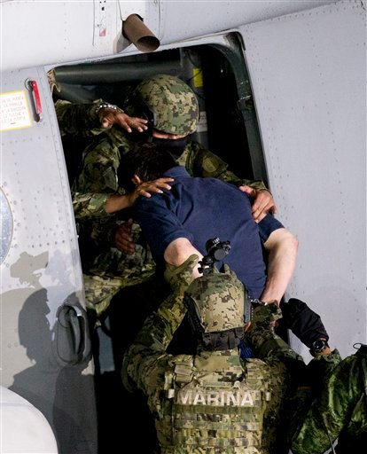 """Mexican drug lord Joaquin """"El Chapo"""" Guzman is loaded into a marine helicopter at a federal hangar in Mexico City, Friday, Jan. 8, 2016. The world's most wanted drug lord was recaptured by Mexican marines Friday, six months after he fled through a tunnel"""