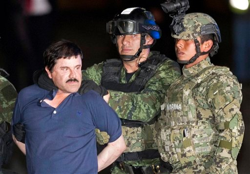 """Mexican drug lord Joaquin """"El Chapo"""" Guzman, right, is escorted by soldiers and marines to a waiting helicopter, at a federal hangar in Mexico City, Friday, Jan. 8, 2016. The world's most wanted drug lord was recaptured by Mexican marines Friday, six mont"""