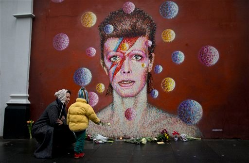 A woman and child place a flower alongside other tributes beside a mural of British singer David Bowie by artist Jimmy C in Brixton, south London, Monday, Jan. 11, 2016. (AP Photo/Matt Dunham)