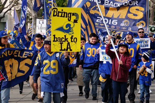 Rams football fans hold banners, wave signs and chant while marching around the historic Los Angeles Memorial Coliseum.