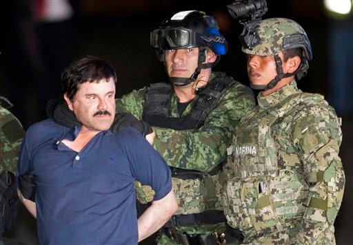 """In this Friday, Jan. 8, 2016 photo, Joaquin """"El Chapo"""" Guzman is made to face the press as he's escorted to a helicopter in handcuffs by soldiers and marines at a federal hangar in Mexico City. Guzman's second prison escape in 2015 from a top security pri"""