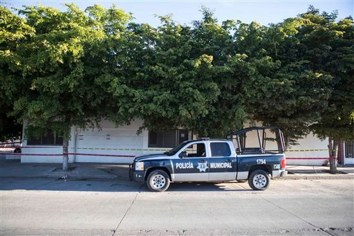 """A police truck sits parked outside the home where marines engaged in a gun battle during the search for Mexican drug lord Joaquin """"El Chapo"""" Guzman, in Los Mochis, Mexico, Sunday, Jan. 10, 2016. Guzman apparently fled from the home Friday before authoriti"""
