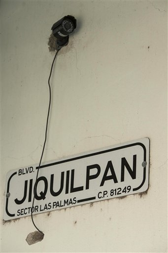 """A security camera sits above a street sign on the exterior wall of the home where marines engaged in a gun battle during the search for Mexican drug lord Joaquin """"El Chapo"""" Guzman, in Los Mochis, Mexico, Sunday, Jan. 10, 2016. A month or two of intensive"""