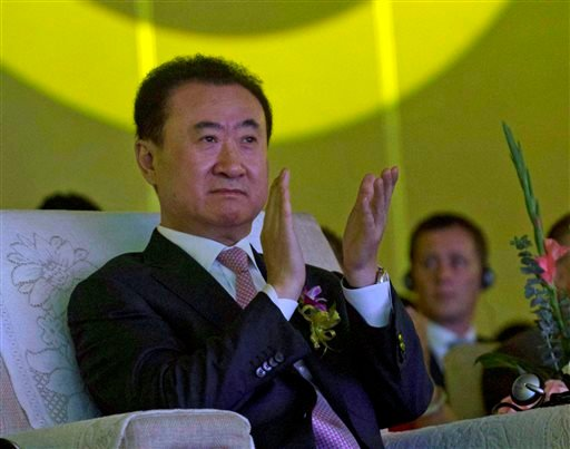 In this June 19, 2013, file photo, Wanda Chairman Wang Jianlin applauds during an event at a hotel in Beijing, China.