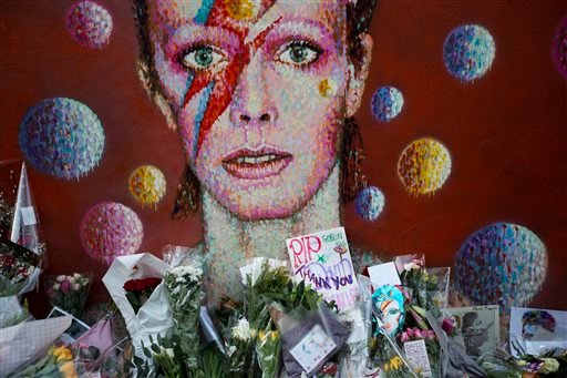 Tributes lie beneath a mural of British singer David Bowie by artist Jimmy C in Brixton, south London, Tuesday, Jan. 12, 2016.