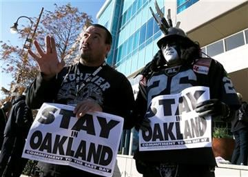 Oakland Raiders fans Griz Jones, left, and Ray Perez make their case for keeping the NFL football team in Oakland outside the hotel where NFL owners are meeting Tuesday, Jan. 12, 2016, in Houston.