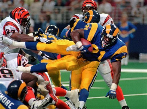 This Sunday, Sept. 1, 1996, file photo shows St. Louis Rams running back Lawrence Phillips (21) leaping over a mound of players as he scores against the Cincinnati Bengals in St. Louis, Mo.
