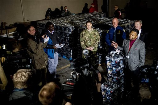 Cameras and reporters surround Flint Fire Chief David Cox, who speaks into microphones atop stacks of bottled water during a press conference on Wednesday, Jan. 13, 2016, announcing the arrival of seven Michigan National Guard soldiers to help aid at Flin