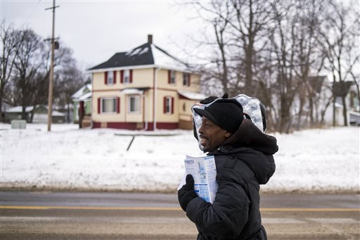 Flint resident Charles Chatmon carries a free water filter and case of water away from a Flint fire station on Wednesday, Jan. 13, 2016 in Flint, as the first seven Michigan National Guard soldiers arrive, assigned by Gov. Rick Snyder on Tuesday to help d