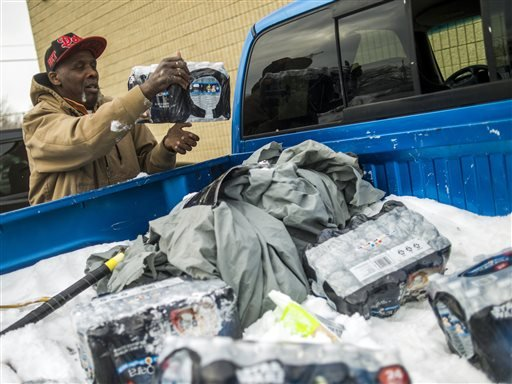 Flint resident Herbert Biggs, 59, throws a case of bottled water in the back of his truck, as he gathers water for his neighborhood on Wednesday, Jan. 13, 2016 at a fire station in Flint, Mich. The first seven Michigan National Guard soldiers are on the g