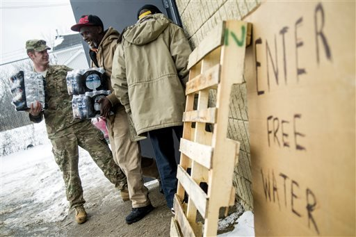Michigan National Guard Staff Sgt. Stephen Robel, left, holds the door open while helping Flint resident Herbert Biggs, 59, as they carry cases of free bottled water to his truck as the first seven Michigan National Guard soldiers are on the ground at fir