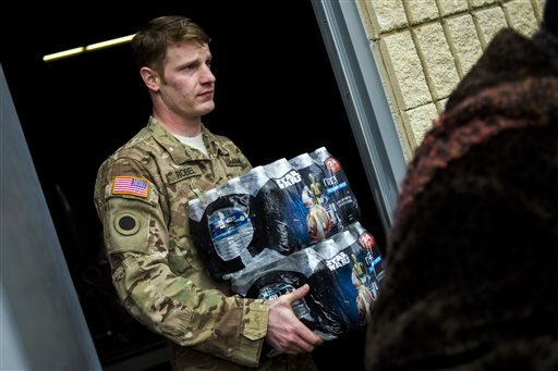 Michigan National Guard Staff Sgt. Stephen Robel helps carry a case of water to the vehicle of Flint resident Karand Houston as the first seven Michigan National Guard soldiers arrive on the ground at fire stations on Wednesday, Jan. 13, 2015 throughout F