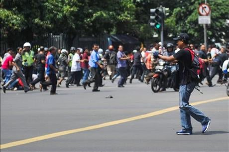 In this photo released by China's Xinhua News Agency, an unidentified man with a gun walks in the street as people run in the background on Thamrin street near Sarinah shopping mall in Jakarta, Indonesia.