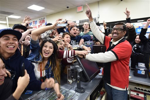 7-Eleven store clerk M. Faroqui celebrates with customers after learning the store sold a winning Powerball ticket on Wednesday, Jan. 13, 2016 in Chino Hills, Calif.