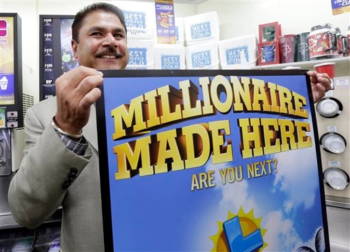 Balbir Atwal, the owner of a 7-Eleven store that sold a winning Powerball lottery ticket, holds up a Millionaire Made Here, sign at his store in Chino Hills, Calif., Thursday, Jan. 14, 2016.