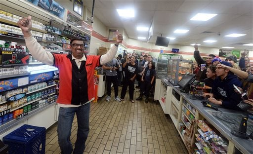 7-Eleven store clerk M. Faroqui celebrates after learning the store sold a winning Powerball ticket on Wednesday, Jan. 13, 2016 in Chino Hills, Calif.