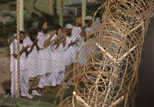 In this May 14, 2009, file photo, reviewed by the U.S. military, Guantanamo detainees pray before dawn near a fence of razor-wire, inside Camp 4 detention facility at Guantanamo Bay U.S. Naval Base, Cuba. Ten prisoners from Yemen who were held at Guantana