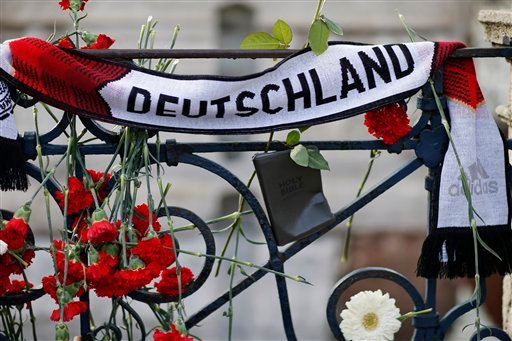 Carnations and a scarf reading Germany that have been left at site of Tuesday's explosion in the historic Sultanahmet district in Istanbul, Thursday, Jan. 14, 2016. A suicide bomber detonated a bomb in the heart of the district on Tuesday morning, killing