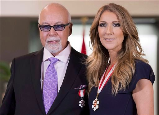 This July 26, 2013, file photo shows Canadian music star Celine Dion, right, and husband Rene Angelil posing for photos after being decorated with the Order of Canada in Quebec City. Authorities say Angelil, the husband and manager of Dion, has died in La