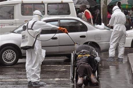 health workers as they spray the body of a amputee suspected of dying from the Ebola virus with disinfectant, in a busy street in Monrovia, Liberia, Tuesday, Sept. 2, 2014.