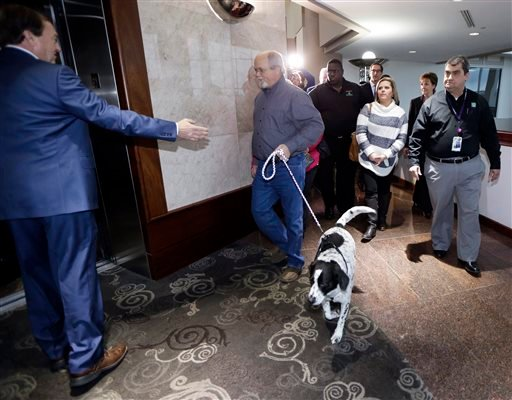 John Robinson leads the family dog as he walks to an elevator at the Tennessee Lottery headquarters, Friday, Jan. 15, 2016, in Nashville, Tenn.
