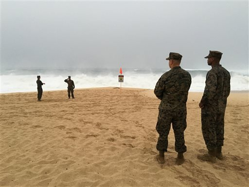 U.S. Marines walk on the beach at Waimea Bay near Haleiwa, Hawaii, where two military helicopters crashed into the ocean about 2 miles offshore, Friday, Jan. 15, 2016.