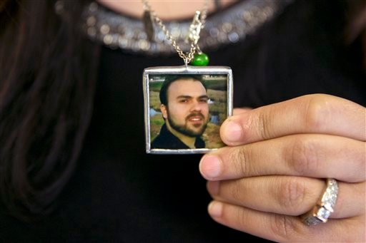 In this June 2, 2015 file photo, Naghmeh Abedini holds a necklace with a photograph of her husband, Saeed Abedini, on Capitol Hill in Washington. Iran state television has reported that the government has released several dual-national prisoners. The Asso